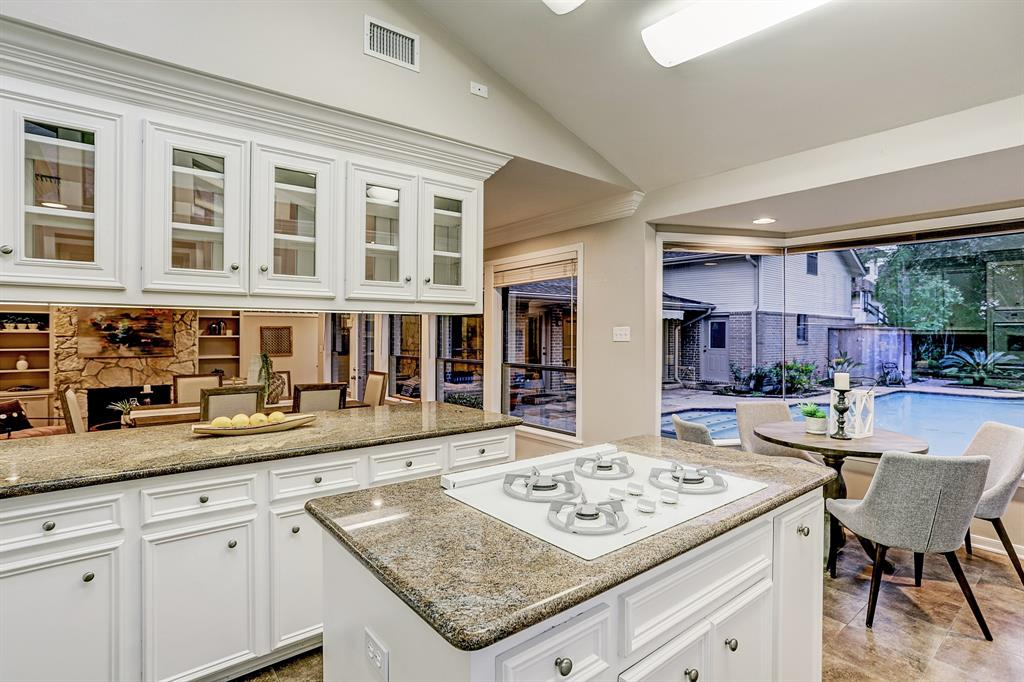 The ISLAND KITCHEN (11\' x 11\') has plentiful storage cabinets, a double oven, a white French door refrigerator and a gas cooktop on the island.  Upper cabinets with double glass doors separate the Kitchen from the Formal Dining Room.  Notice the vaulted ceiling and granite countertops.