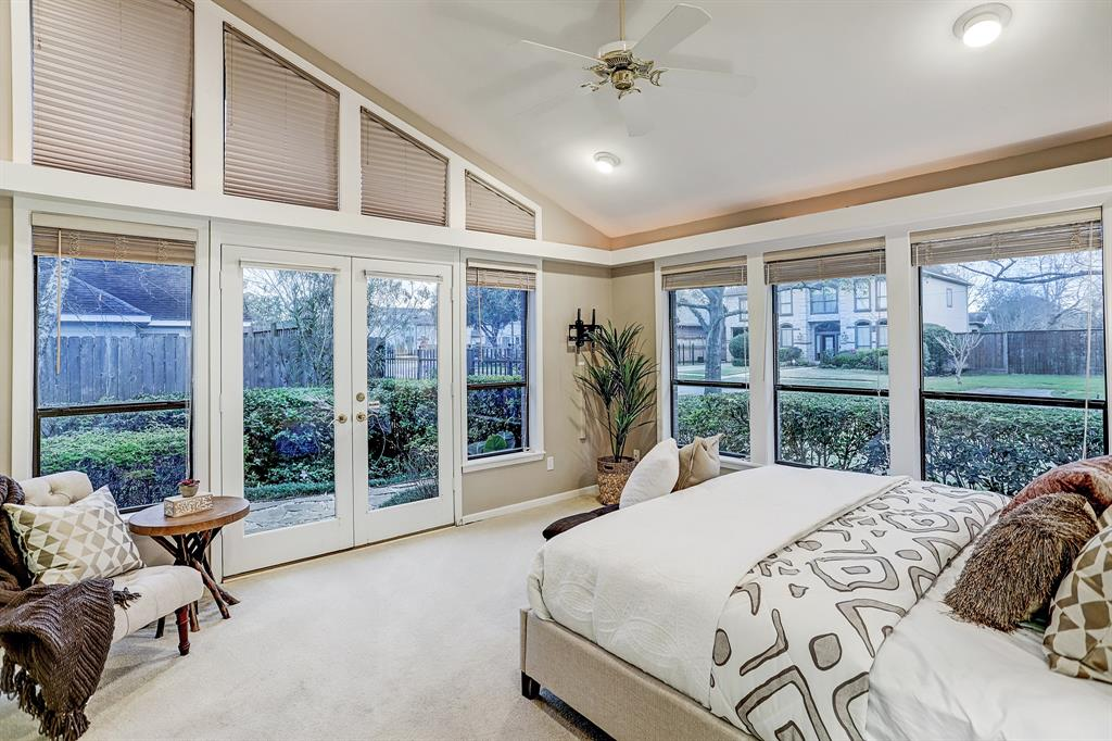 The MASTER BEDROOM (19\' x 13\') is filled with natural light from plentiful windows and has a vaulted ceiling, two walk-in closets and French doors leading to a beautifully landscaped side yard.