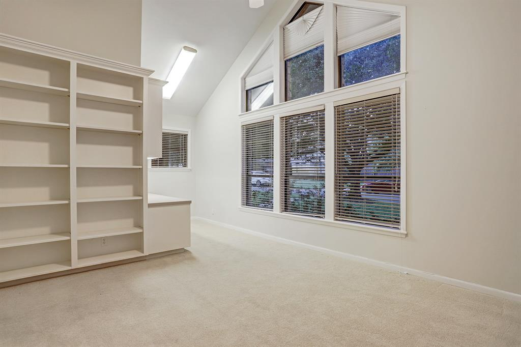 Another view of the previous SECONDARY BEDROOM (14\' x 12\') that highlights the large windows and plush neutral carpeting.