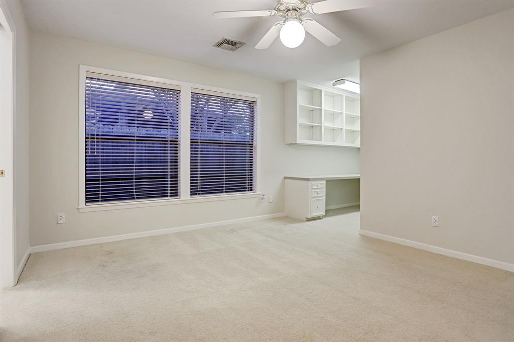 Another SECONDARY BEDROOM (14\' x 12\') that has a built-in desk and upper open shelving, and two large windows.