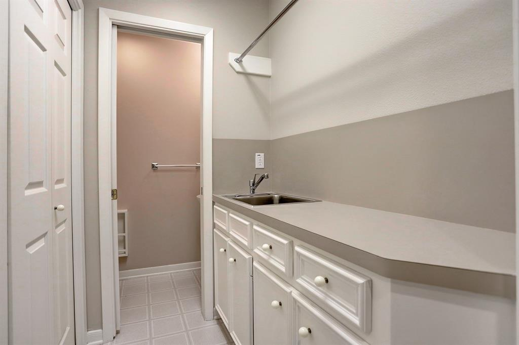 Close to the Family Room is the LAUNDRY ROOM (with a sink and hanging rod) and there is a HALF BATH through the open pocket door.
