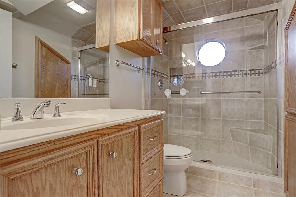The EN SUITE BATH for the 4th Bedroom has  a large walk-in shower and plenty of storage cabinets.