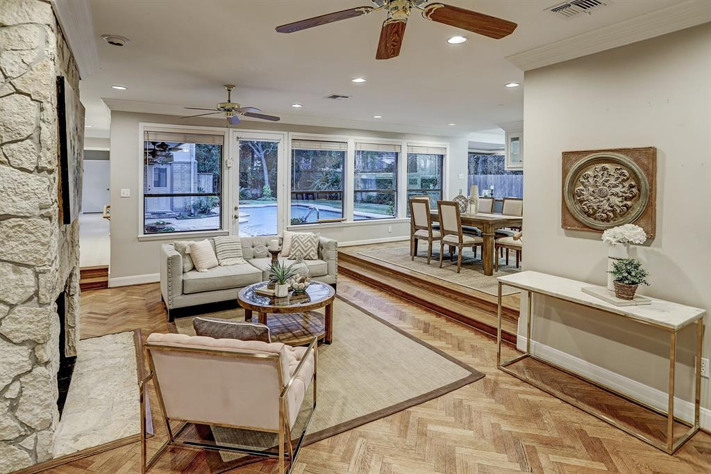 The Living Room and Dining Room are bathed in natural light from a wall of windows and a door that opens to the Backyard.