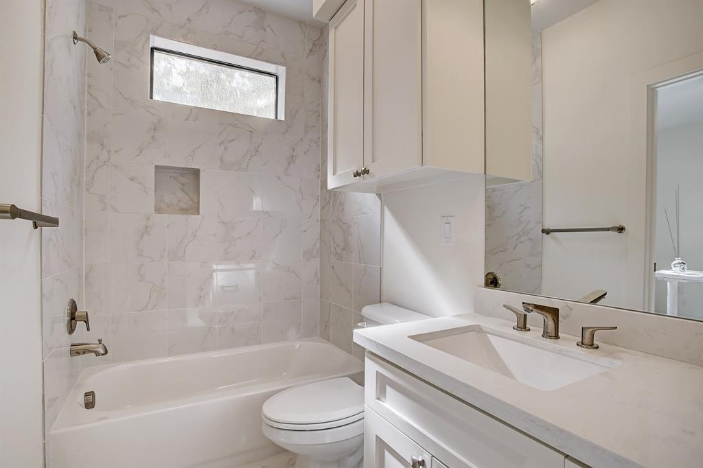 Full bath with tub - shower combo is off of the first story living space complete with quartz countertops and faux marble porcelain tiles