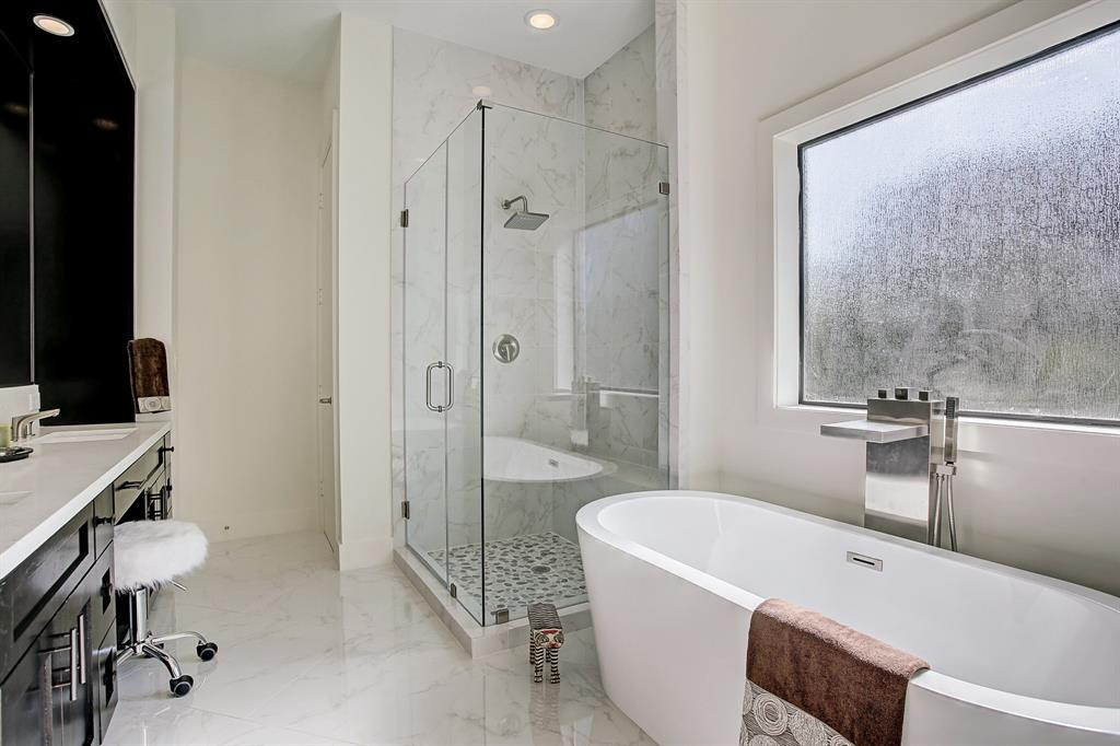 Large master bath complete with oversized glass enclosed shower with rain bath shower head and relaxing soaker tub...love all the natural light