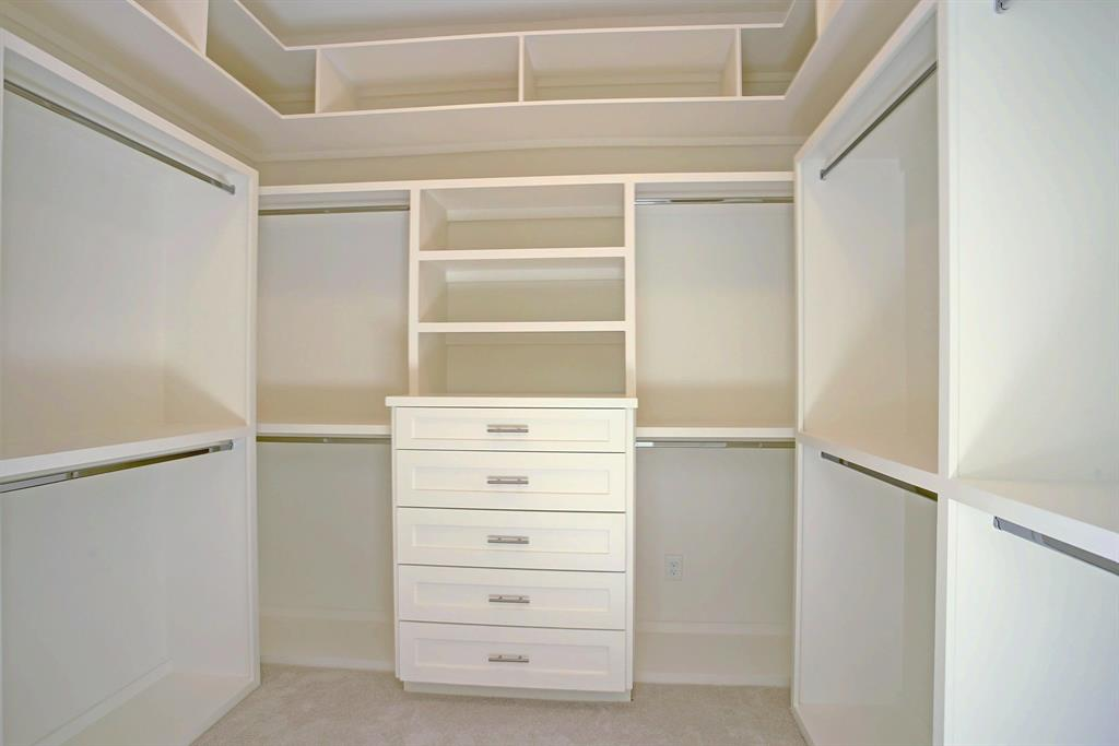 Dream closet with plenty of storage and upper storage for out of season items