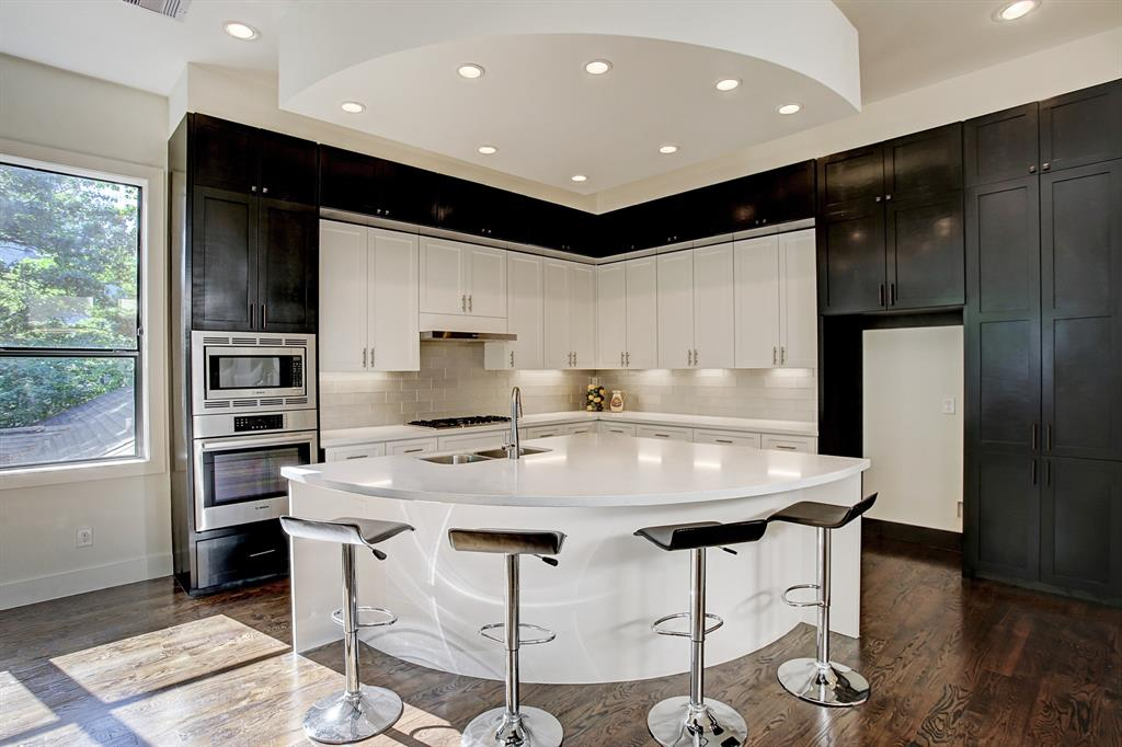 The kitchen island is an inviting area to have a casual dining experience, note the glass \