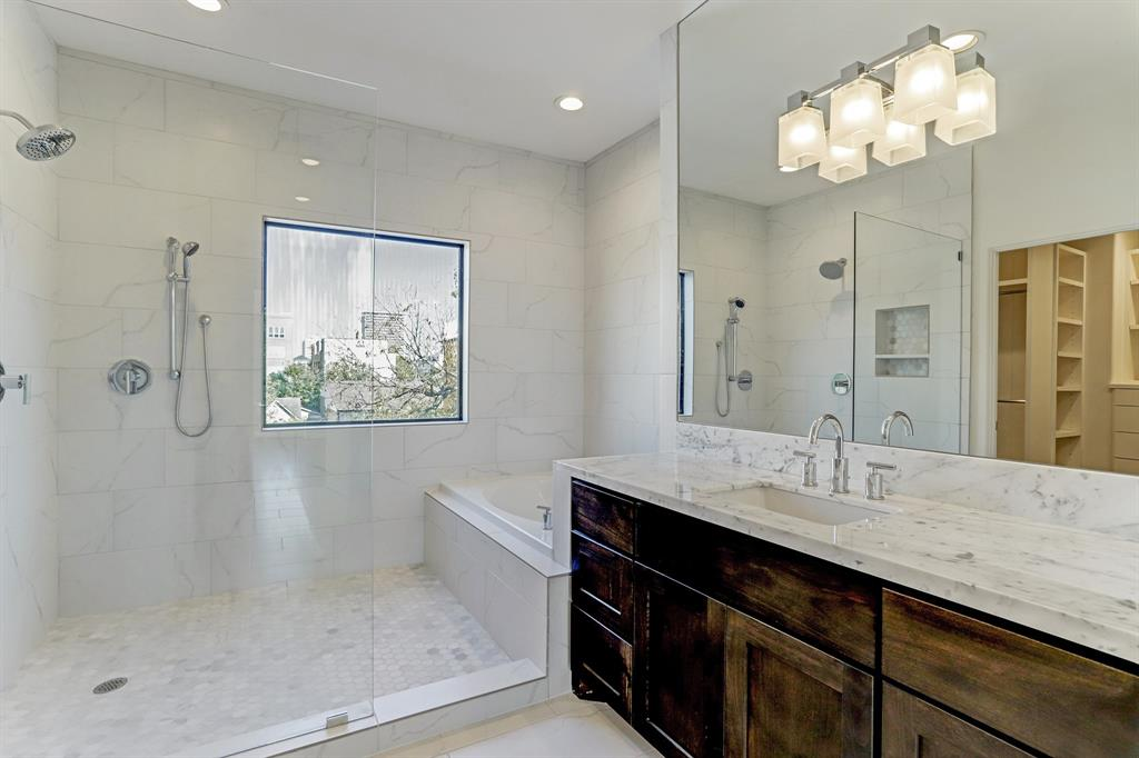 Modern style and design abound in the magnificent master bath draped in Marrazi Porcelain tile flooring with his and her vanities boasting Carrera marble counters and designer fixtures and lighting.