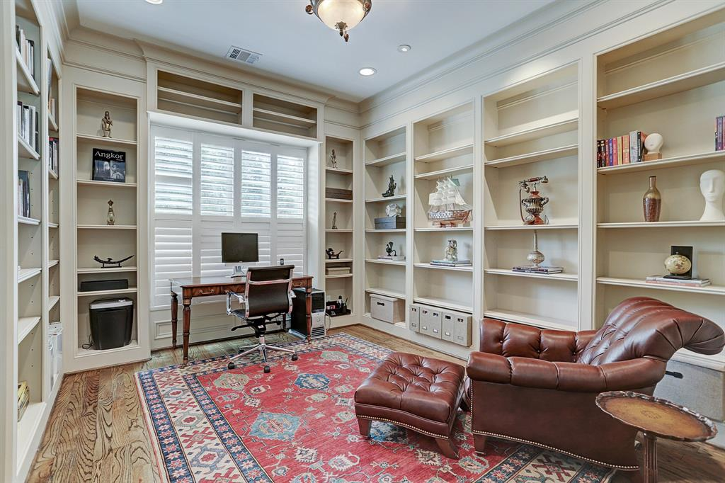View of the STUDY looking to large window with plantation shutters.  Note the designer F Raymond ceiling light fixture.  Cove lighting, crown molding and hardwood floor.