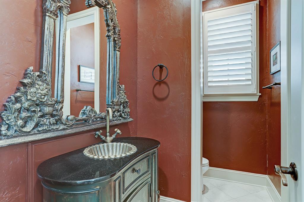 POWDER ROOM - 8x5 - owners hand selected this gorgeous framed antique mirror above the custom stand-alone decorative sink  with granite surface and cabinetry beneath.  Separate toilet area with additional cabinetry.