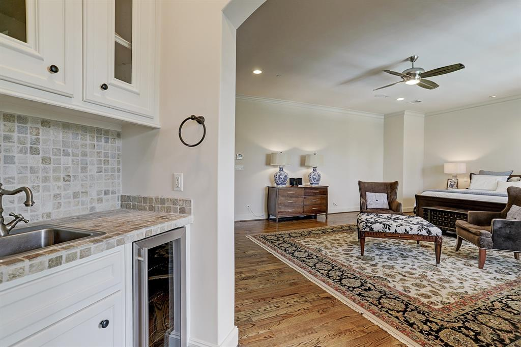 Between the master suite and master bath is wet bar with stone tile counter and backsplash plus a built-in Marvel wine refrigerator.  Brushed nickel sink with cabinetry above and below.   You will not want to leave your master retreat!