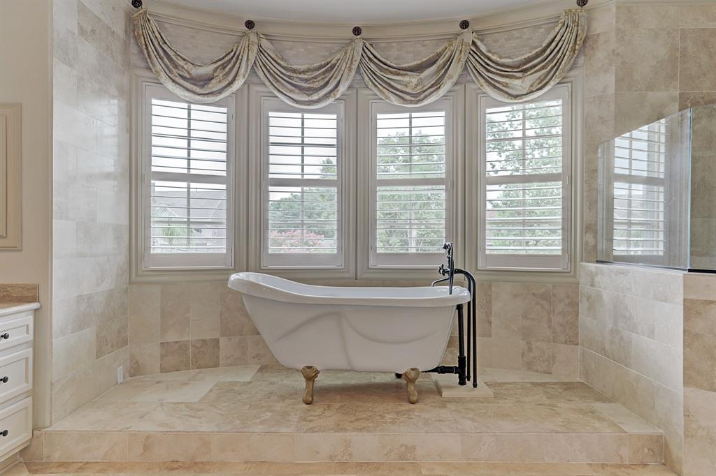 Soak in the porcelain claw-foot tub  - on an elevated surface - with oil-rubbed bronze hardware beneath a curved bay window with plantation shutters.  Note the decorative silk valances above the windows.