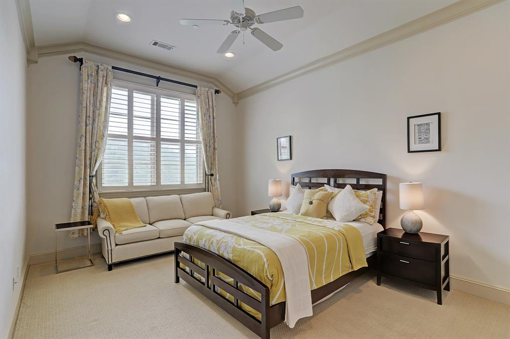 SECONDARY BEDROOM with ensuite bathroom - 17x12 - has a vaulted ceiling, carpet, ceiling fan, crown molding and a large window with plantation shutters.