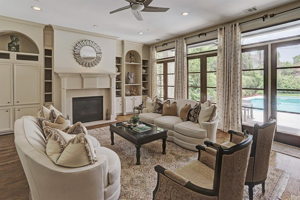 Beautiful custom built-ins and travertine surround fireplace accent the FAMILY ROOM - 24x20.  Tall French doors look to the covered slate patio and pool.   A spacious area to visit with friends and family.