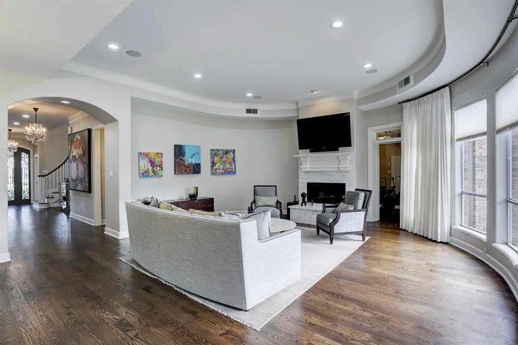 Large open family room with lots of natural light.  The gas log fireplace has marble surround and hearth.  The flex room is towards the upper right.