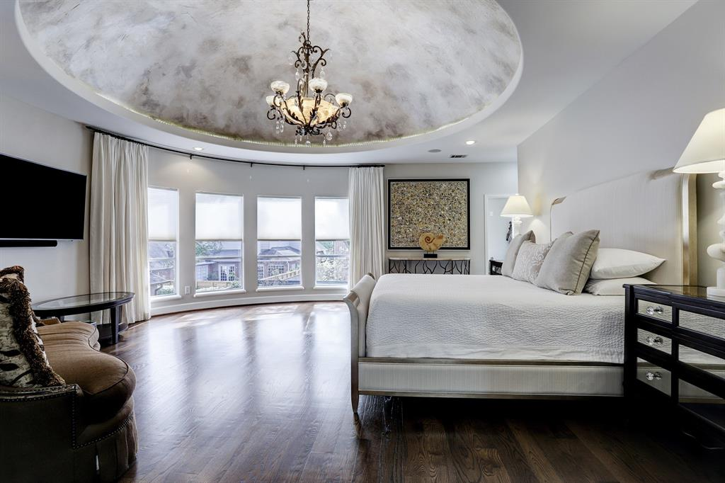 The spacious master suite has plenty of room  and features a dramatic dome ceiling, hardwood floors, beautiful wrought iron chandelier and wall of windows with views of the backyard.