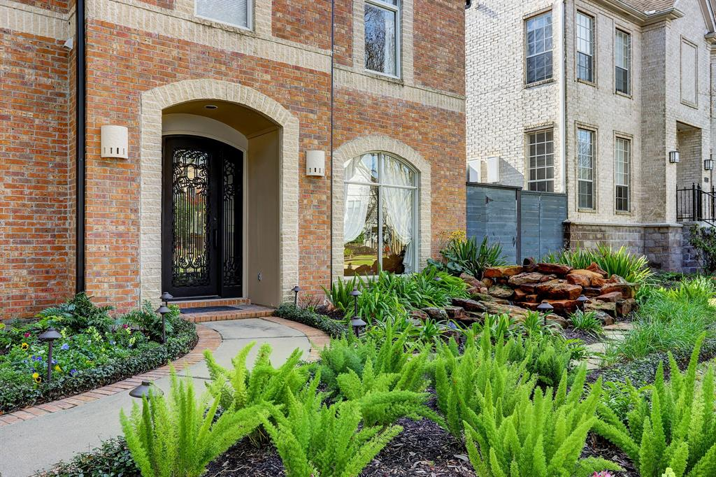 The front exterior features beautifully landscaped gardens and a custom iron front door.