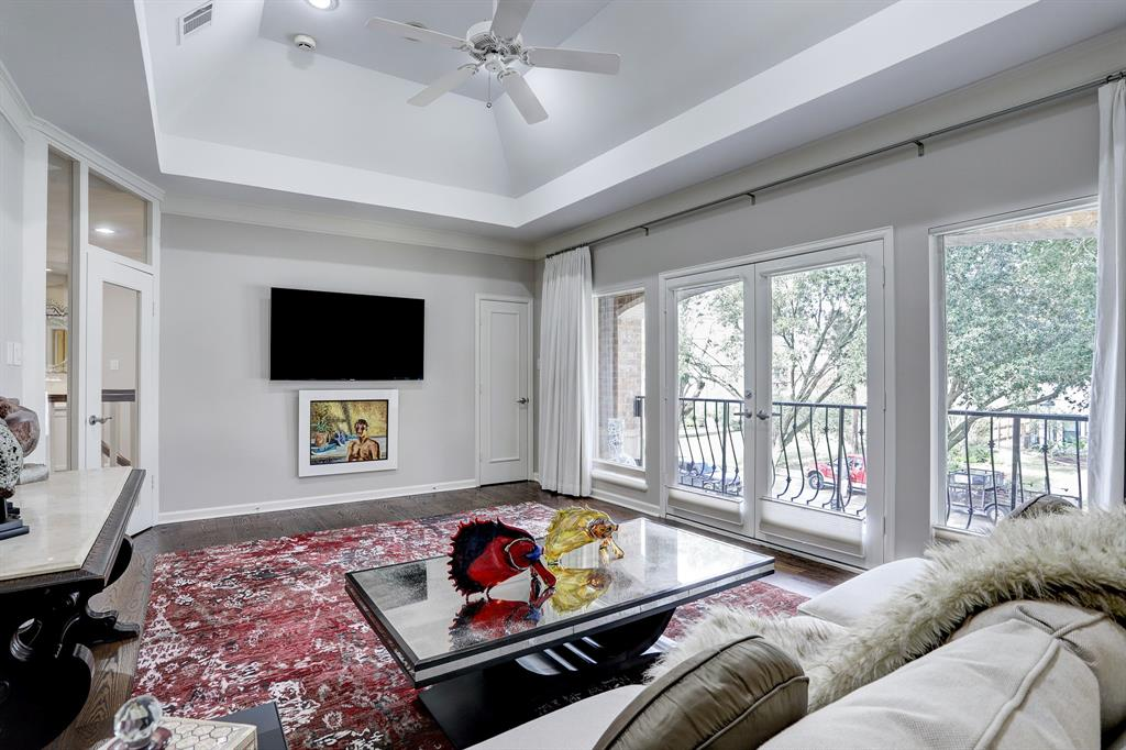 The second floor game room features vaulted ceilings, hardwood floors, game closet and wall of windows and double French doors with views of the front.