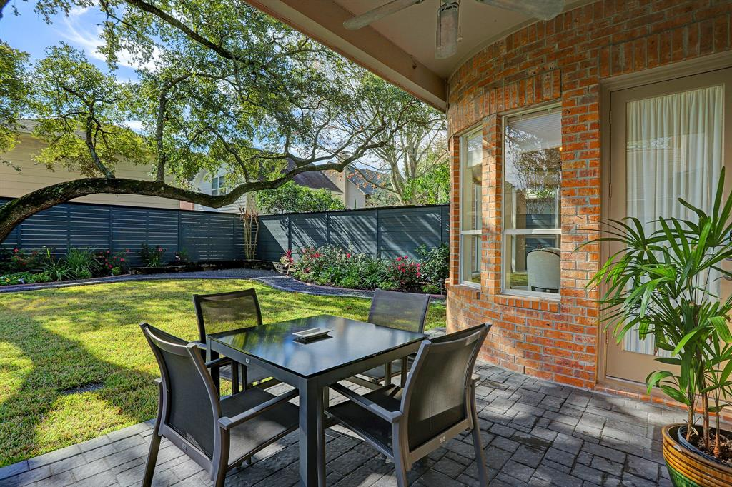 Covered patio with ceiling fan and views of the fabulous backyard!