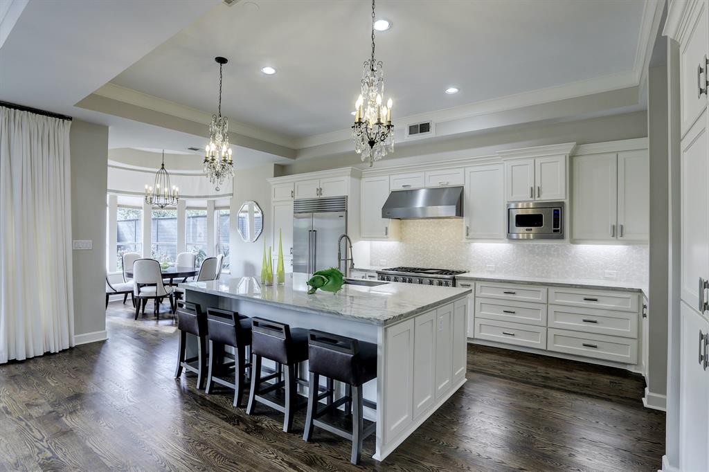 Another view of the kitchen looking towards the breakfast room.  Note the beautiful light fixtures and slab island.