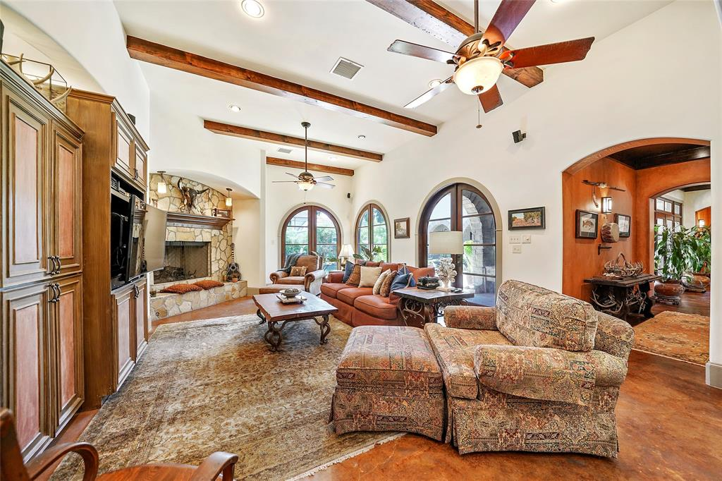 Family room features a stone fireplace, large built in cabinet for TV and storage and high arched windows that offer a view of the beautiful pool area. The far right arches are double doors opening to the patio/pool area.