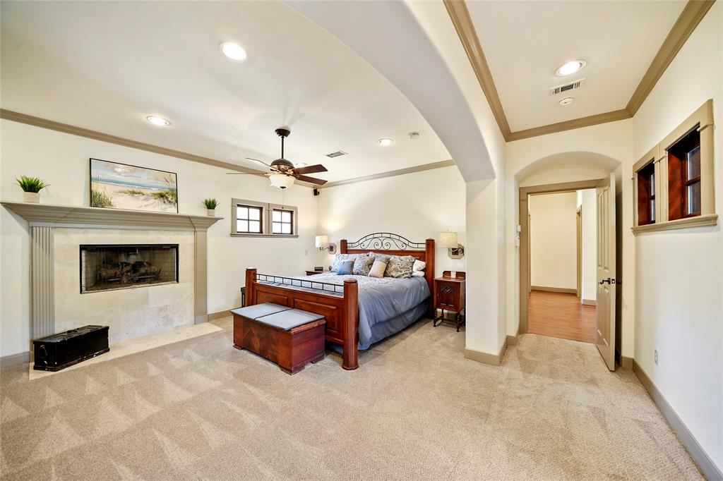 Huge Master bedroom features crown moulding, travertine facing on the fireplace and convenient swing arm sconce lighting at the head of the bed.