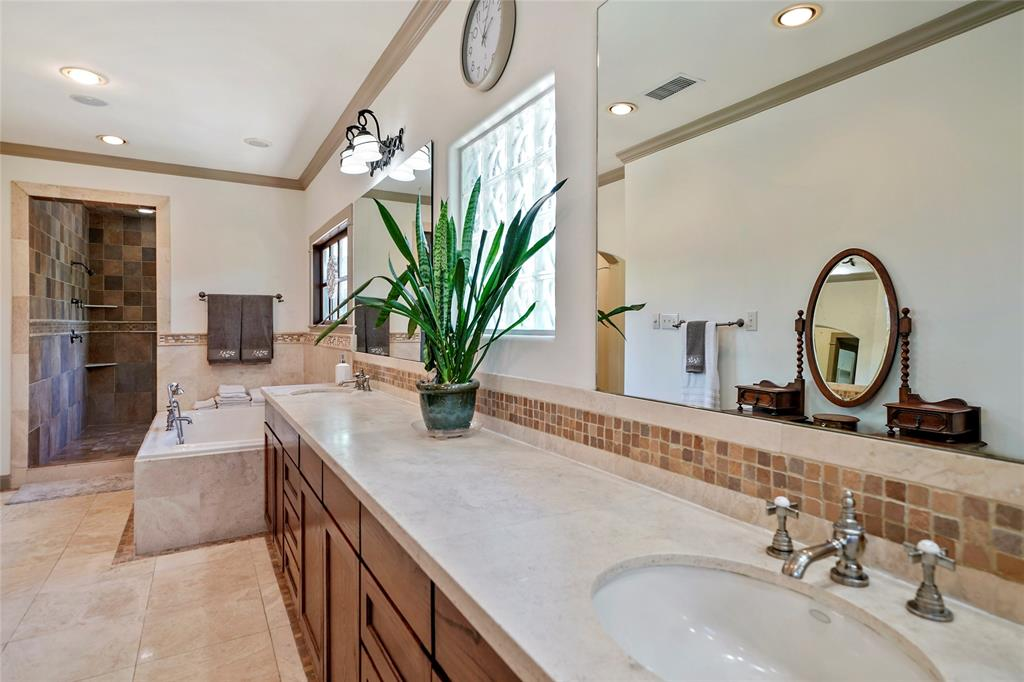 Master Spa retreat features travertine flooring and stone accents, an oversized whirlpool tub, double sink travertine vanity, makeup area and coffee bar and bidet.
