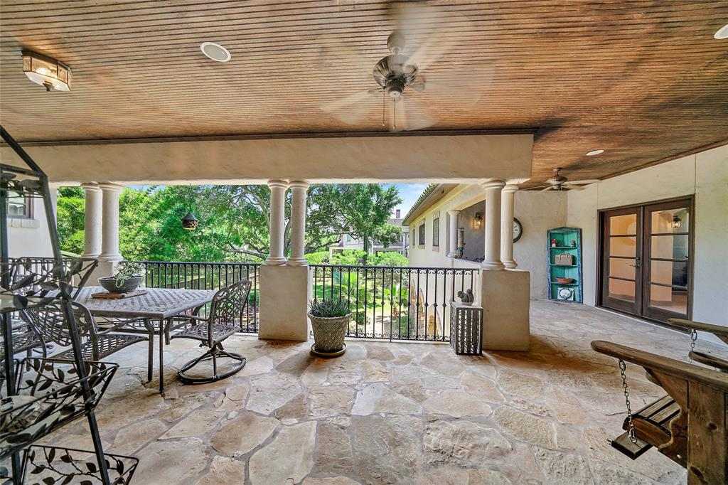 Beautiful upstairs patio area overlooks the beautiful pool area below. The French doors on the right lead into the Master Suite.