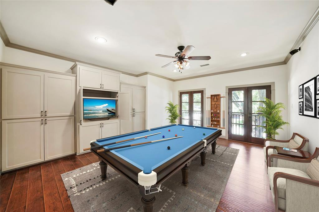 Large Gameroom features lots of built ins, 2 balcony doors, that open to the front yard and new engineered wood flooring.