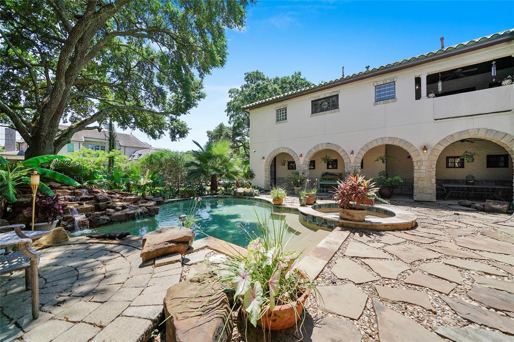 Backyard paradise features heated pool with natural stone waterfall, hot tub and an outdoor pool bathroom.