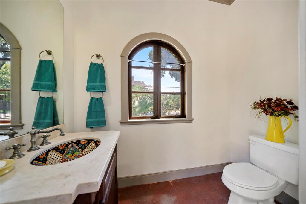 Pool bathroom features travertine vanity with mosaic tile sink and low maintenance stained concrete floors.
