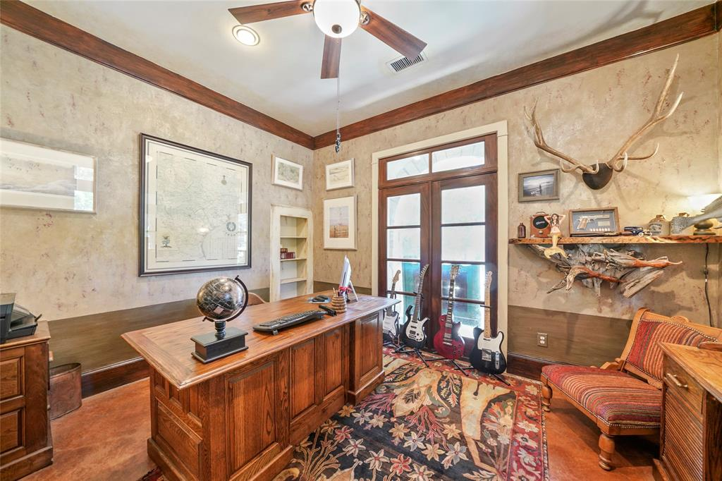French doors open to this private study that features a hidden storage room behind the bookcase.