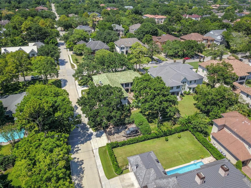 Back aerial view shows the corner lot location with an abundance of mature trees and the additional gated parking area.