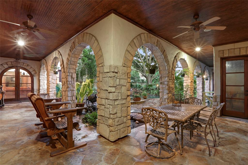 Downstairs patio features flagstone flooring, lots of rock arches, wood ceilings and resort like view of the pool and gardens.