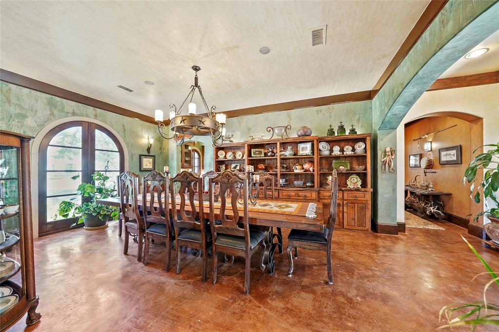 Massive banquet sized formal dining features high end faux paint, arched windows and view of pool area.