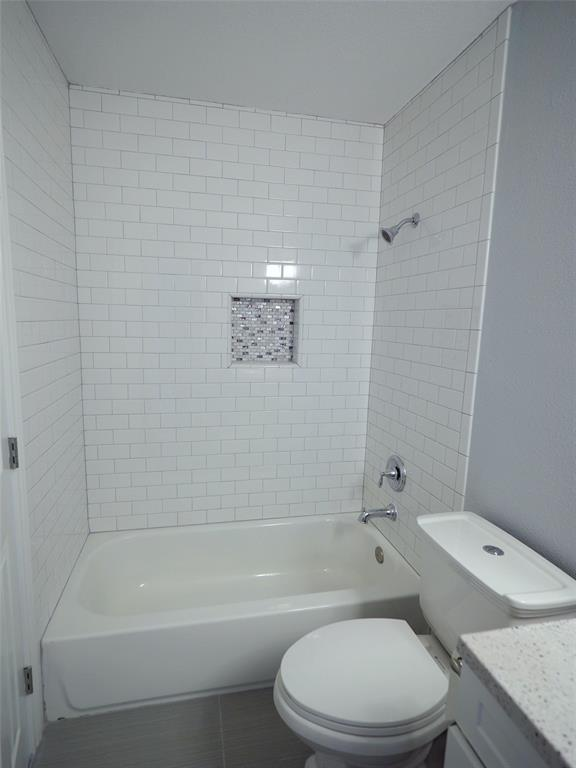 GLEAMING SUBWAY TILE  BACKING SHOWER.  ACCENTED WITH ELEGANT GLASS MOSAIC TILEFOR SOAP/ SHAMPOO HOLDER
