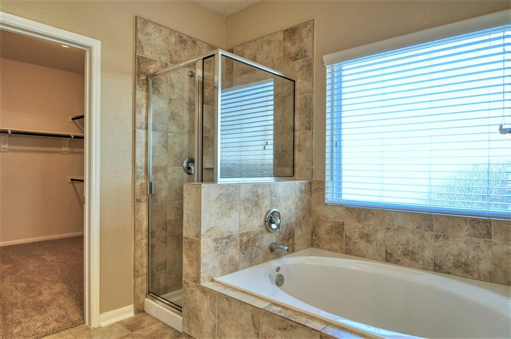 Master Bath has a Separate Shower with oversize Tile Surround for the Wet Area. Large Window for Natural Lighting.