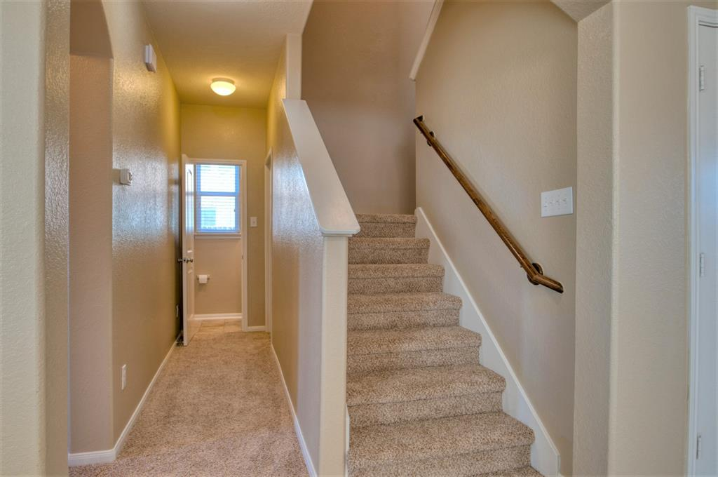 This view shows the 1/2 Bath at the end of the Hallway. Carpeted Stairway leading to the Generous 2nd Floor.