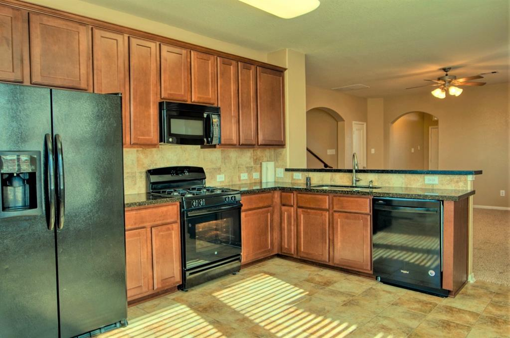Kitchen features 42\' Cabinets complete with Granite Counters and Tile Backsplash.