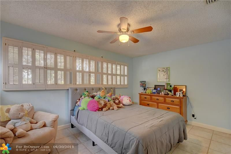 See how spacious the second bedroom is, with it\'s own bathroom and wall of windows.  The floor is the same practical tile as the upstairs hallway.
