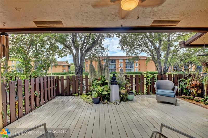 Private patio features long-lasting decking, with lush landscaping, water view and plenty of room for backyard relaxation.