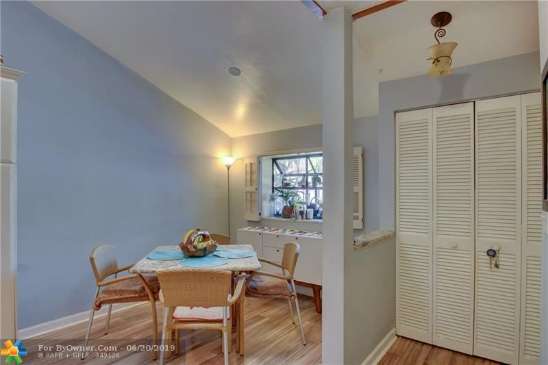 Looking towards the foyer with a closet. Open breakfast area has vaulted ceiling and a great view of the lushly landscaped community.