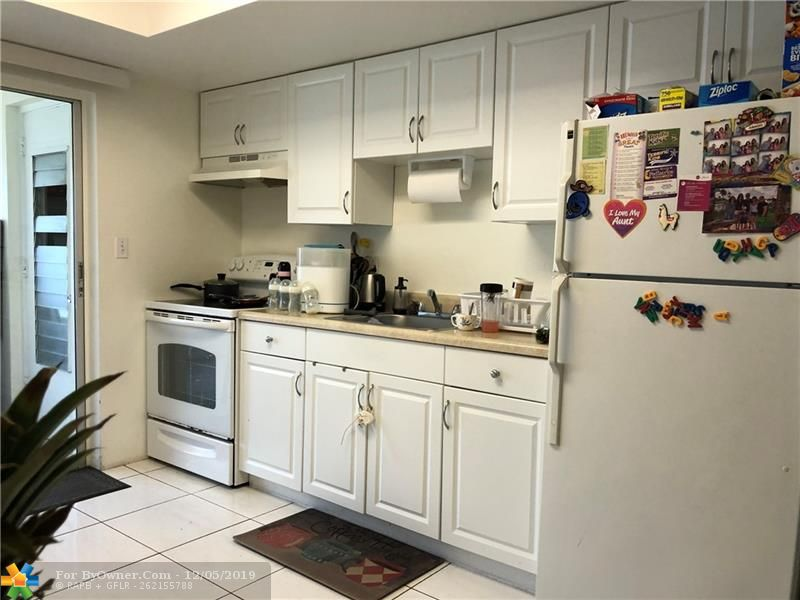 Kitchen with newer white cabinets in both units.