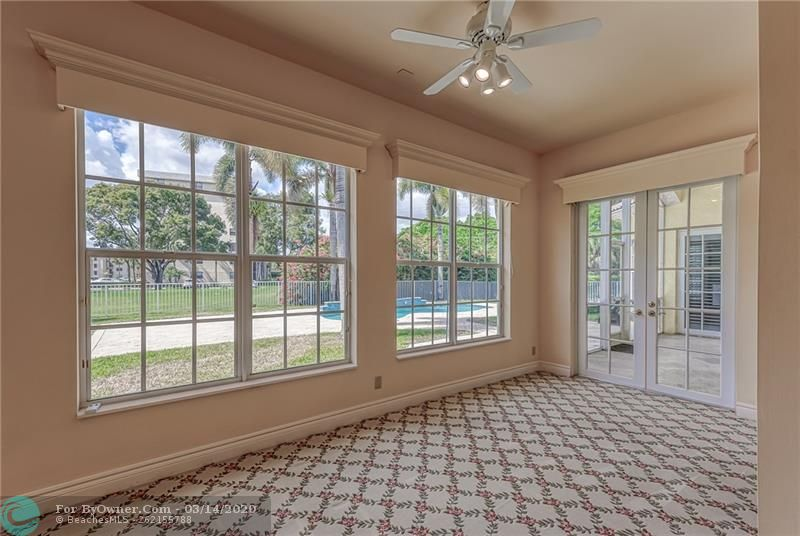 Large sitting area with french doors to porch and pool