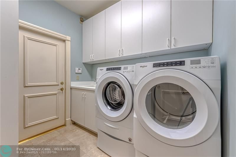 Large front loading washer and dryer in laundry room with extra storage