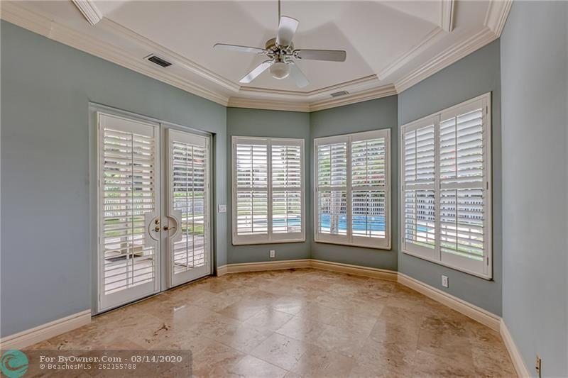 Family room with plantation shutters and french doors that lead to the pool