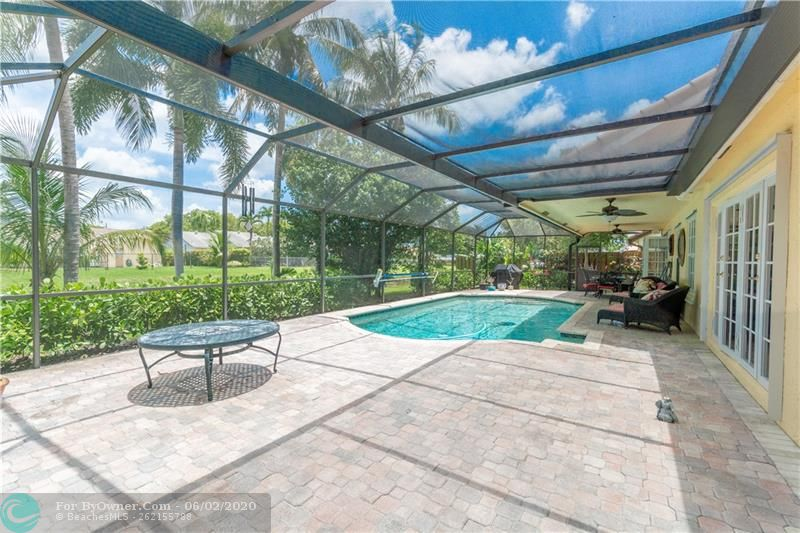 Living room has French doors leading to pool/patio entertainment area