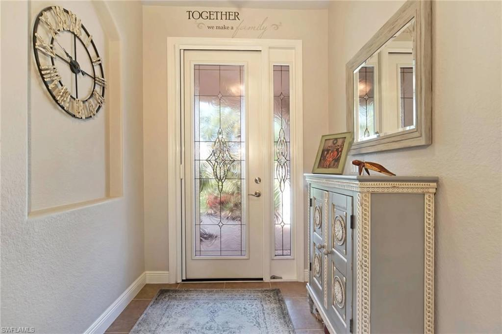 Foyer with beautiful impact glass door and tray ceilings.