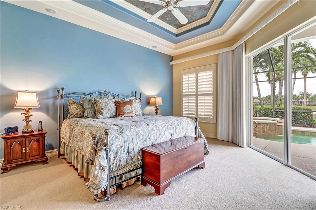 Master bedroom with beautiful views and plantation shutters, Sliders to the patio, tray ceiling with crown molding