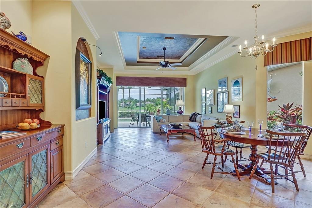 open floor living and dining, tile on the diagonal, crown molding in room as well as tray ceiling, custom shades on all windows and sliders
